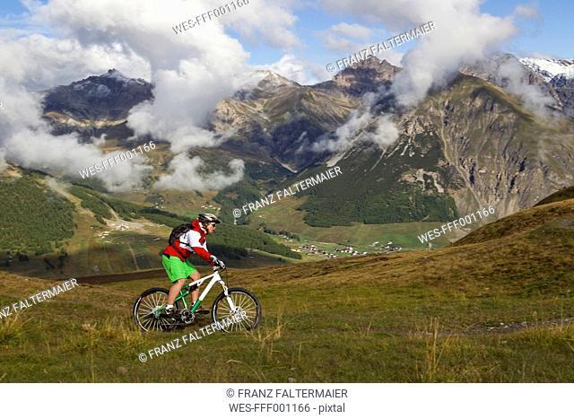 Italy, Livigno, View of woman riding mountain bike