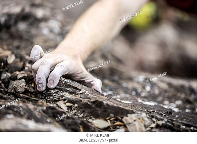 Hand of Caucasian man rock climbing