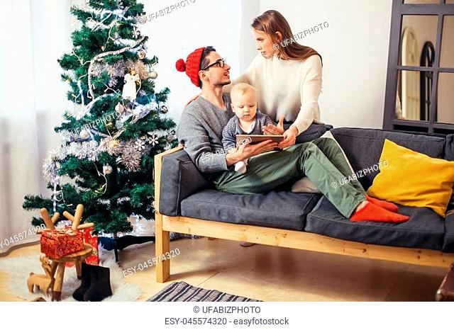 Christmas morning, cheerful family sitting in the living room having fun with the digital tablet that Santa Claus brought her