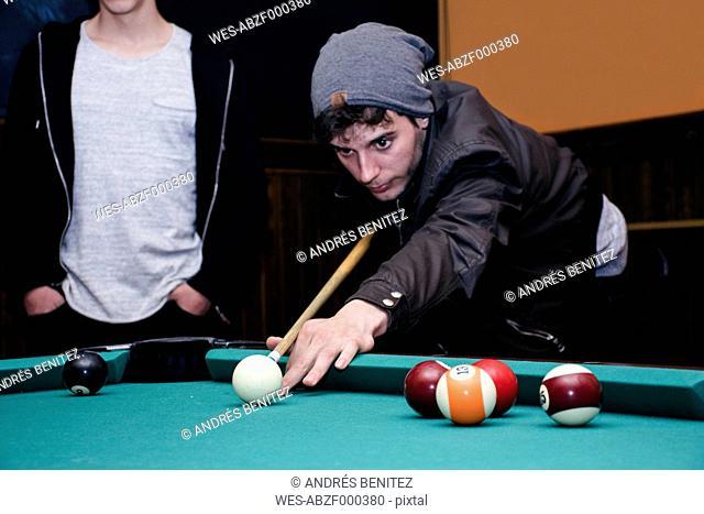 Man playing pool billard with friends in a bar