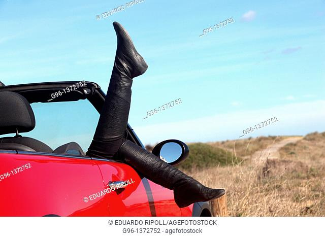 woman in a convertible relaxing at the beach