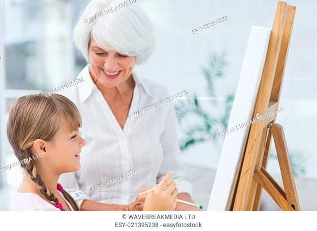 Grandmother and cute granddaughter painting together at home