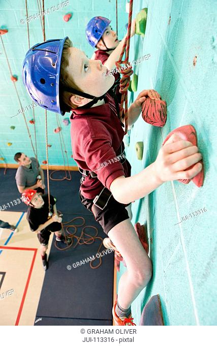 Boys climbing rock climbing wall