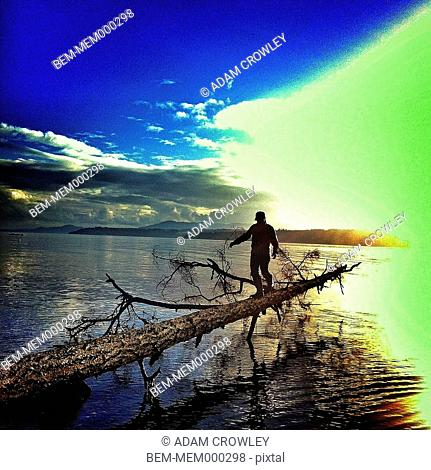 Man balancing on log over lake, Duncan, British Columbia, Canada