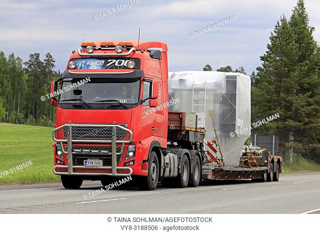 Uurainen, Finland - June 15, 2018: Red Volvo FH16 700 semi trailer delivers industrial object as wide load along highway 4 on overcast day of summer