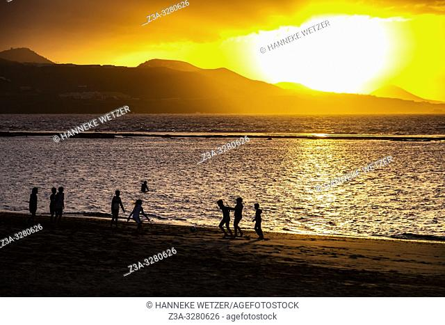 Children playing on the beach during sunset at the coastline of Las Palmas de Gran Canaria, Canary Islands