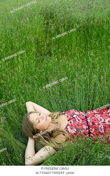Young woman napping in tall grass