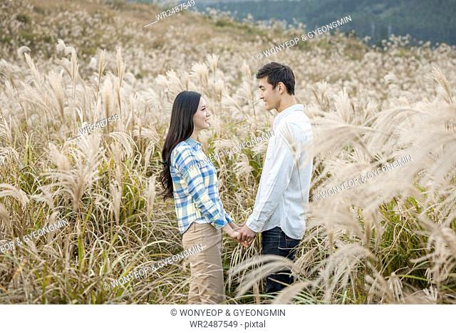 Side view of young smiling couple standing face ro face holding hands in silver grass field