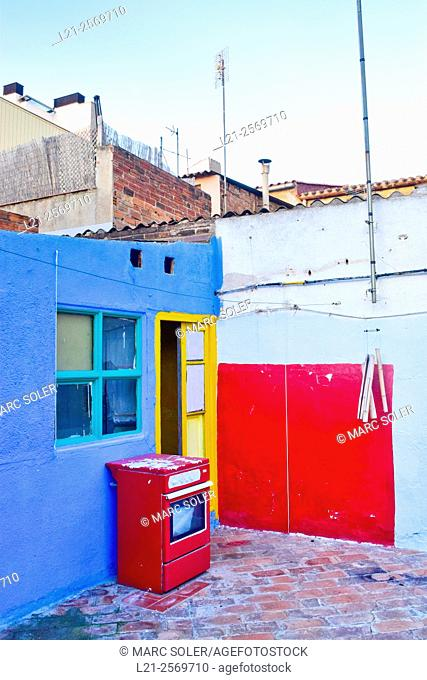Terrace. Blue wall, yellow door, blue window, red wall. Red old stove. Barcelona province, Catalonia, Spain