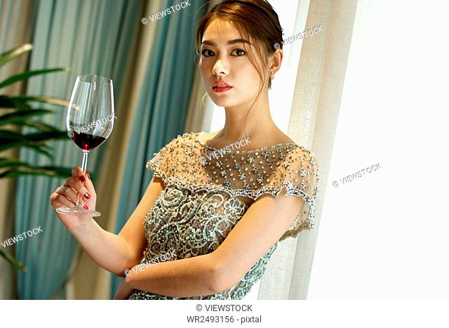 A beautiful young woman holding goblet