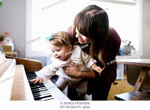 Mother with daughter (12-17 months) playing piano