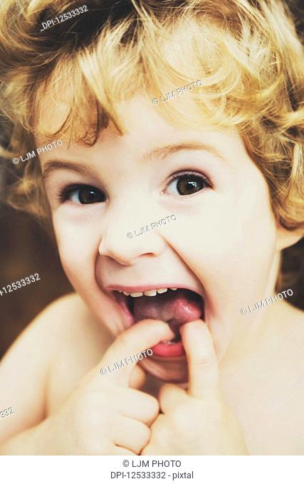 Toddler Making Funny Faces At The Camera And Putting His Fingers in His Mouth; Langley, British Columbia, Canada
