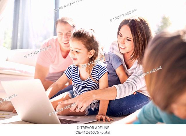 Family using laptop in sunny living room