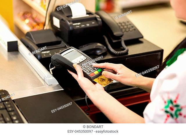 Woman hand with credit card swipe through terminal for sale, in market. Shopping and retail concept