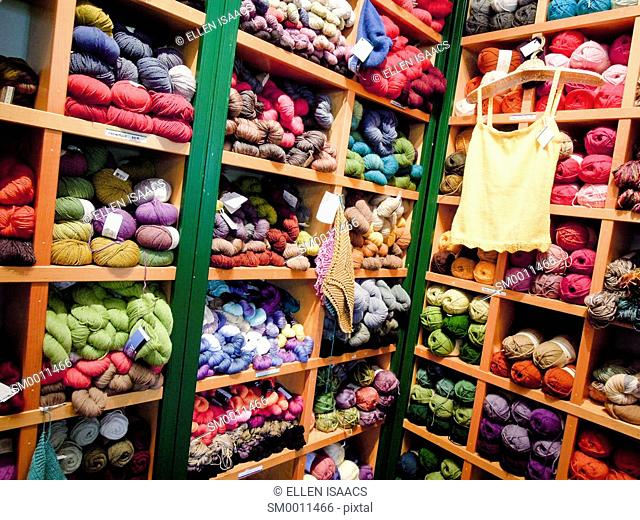 Many colorful skeins of yarn on display in cubbies at a knitting store