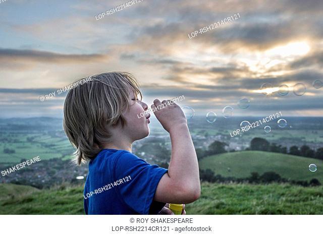 England, Somerset, Glastonbury. A boy blowing bubbles on Glastonbury Tor
