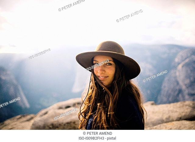 Portrait of young woman at top of mountain, overlooking Yosemite National Park, California, USA