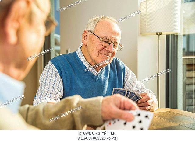 Two senior friends playing cards