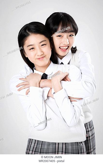two girls posing in school uniforms