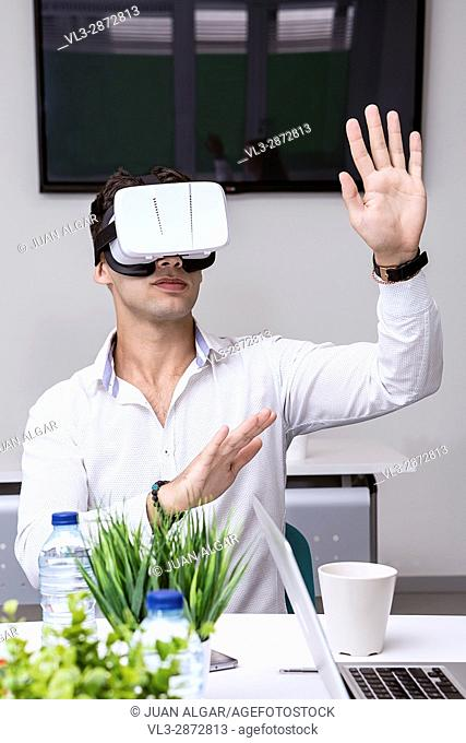 Young man in white shirt gesturing with hands while sitting at table and wearing VR headset