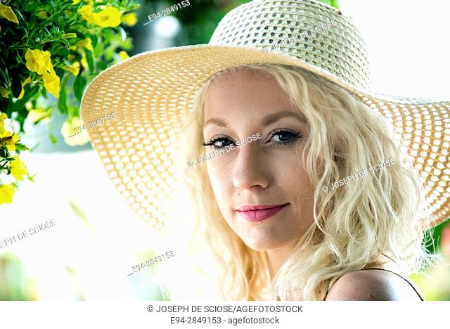 A portrait of a pretty 30 year old blond woman wearing a straw hat smiling at the camera