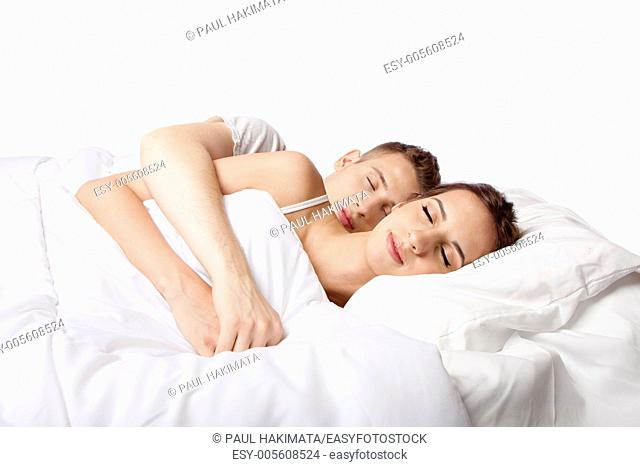 Young couple happily sleeping in white bed, isolated