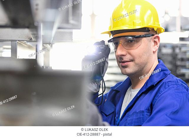 Worker in protective workwear using flashlight in factory