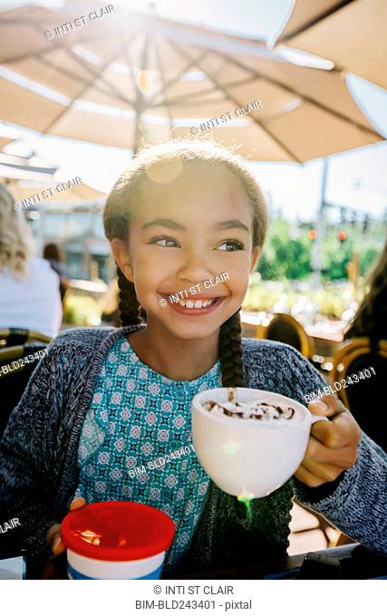 Smiling Mixed Race girl drinking from cup in restaurant