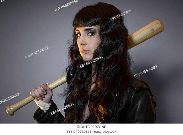 adolescence and delinquency, brunette woman in leather jacket and baseball bat with challenging aptitude