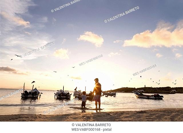 Venezuela, Isla Margarita, Juan Griego, little boy and his grandfather standing at seafront by sunset