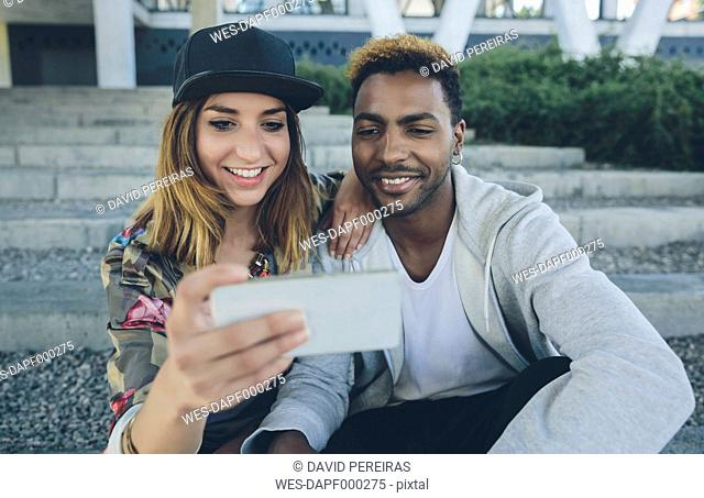 Smiling young couple sitting on steps looking at smartphone