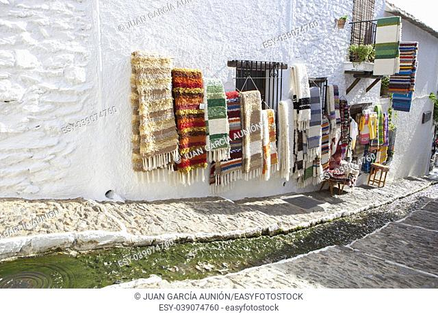 Jarapas for sell displayed over walls at quiet pretty street with water channel in the middle, Alpujarras, Granada, Spain
