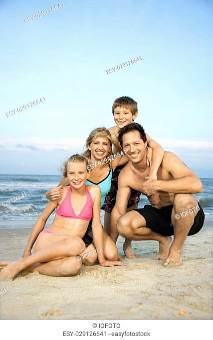 Caucasian family of four posing together on beach