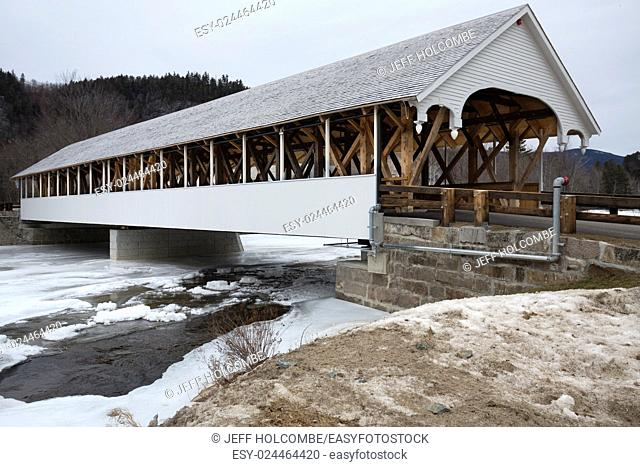 Historic white covered bridge dating to the mid-19th century in Stark, New Hampshire in winter, with ice in the Upper Ammonoosuc River