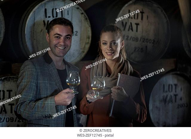 Portrait of smiling man and woman tasting wine