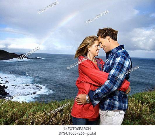 Caucasian mid-adult couple embracing by ocean with rainbow in background in Maui, Hawaii