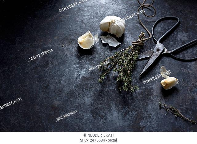 An arrangement of thYesme, garlic and scissors