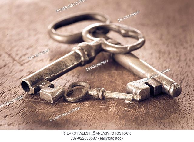 Different keys in old vintage retro style on wooden surface. Set of three from small to large. Symbol of safety, variety and difference