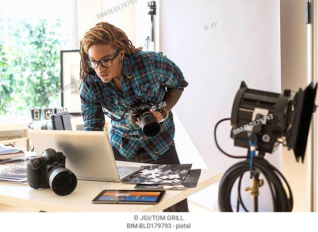 Mixed race photographer using laptop in studio