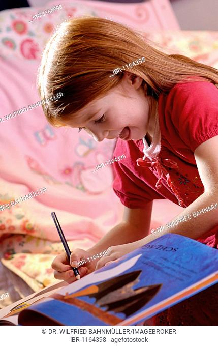Little girl holding a pencil in her hand and writing or drawing