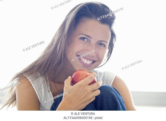 Woman holding apple, smiling, portrait
