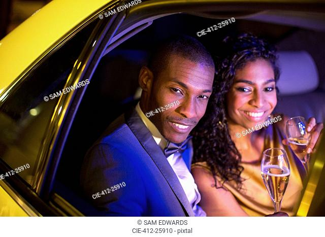 Well-dressed couple drinking champagne inside limousine