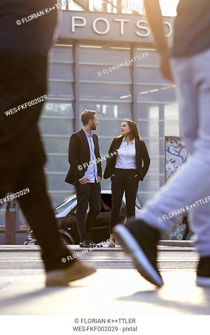 Young businesswoman and businessman talking outdoors