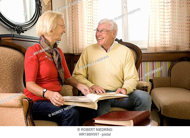 Senior couple looking at photographs in nursing home, Bavaria, Germany