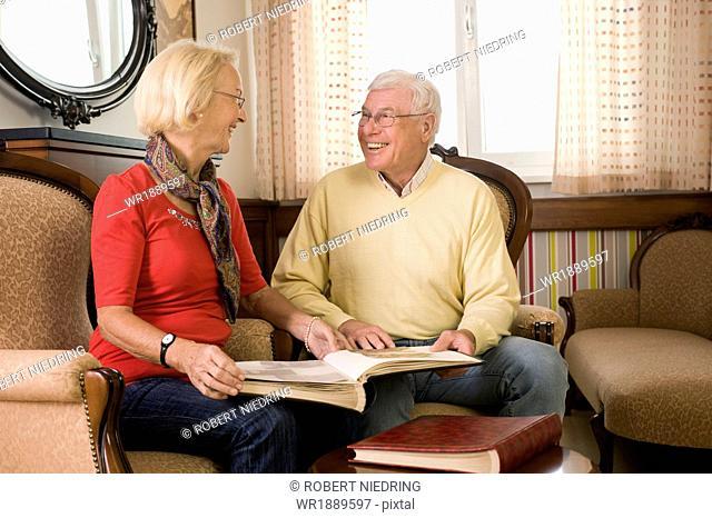 Senior couple looking at photographs in nursing home, Bavaria, Germany