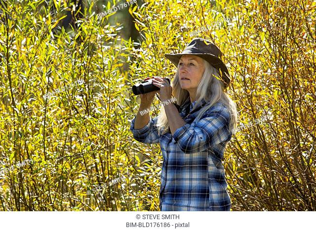 Caucasian woman using binoculars