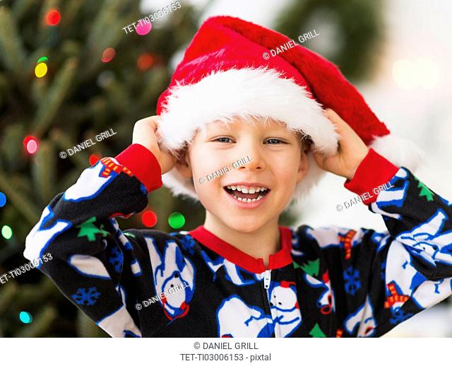 Boy (6-7) wearing santa hat