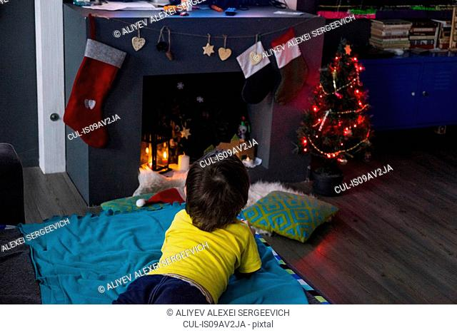 Rear view of male toddler lying on blanket gazing at christmas tree in front of fireplace