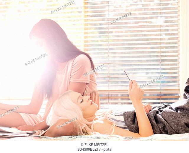 Young woman, looking at smartphone, resting head on female friend's leg