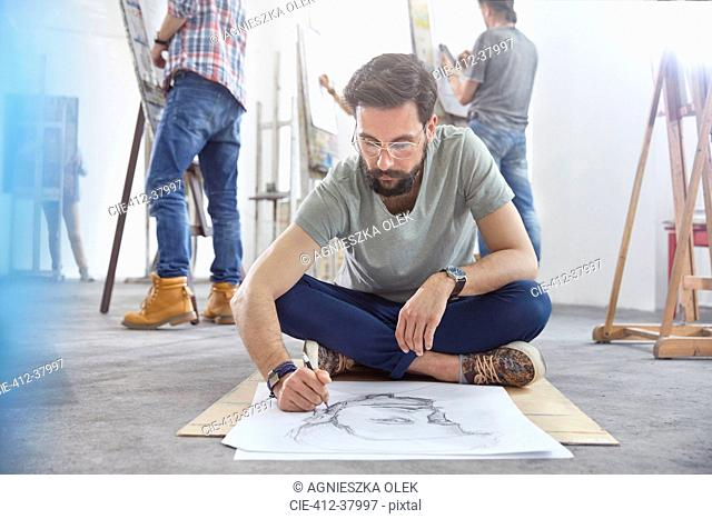 Male artist sitting cross-legged sketching on floor in art class studio
